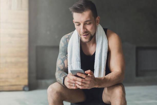 knappe man mobiele telefoon gebruiken in de sportschool - call center stockfoto's en -beelden