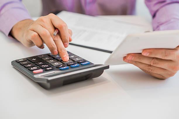 handsome man using a calculator and writing in his notebook - gerente de cuentas fotografías e imágenes de stock