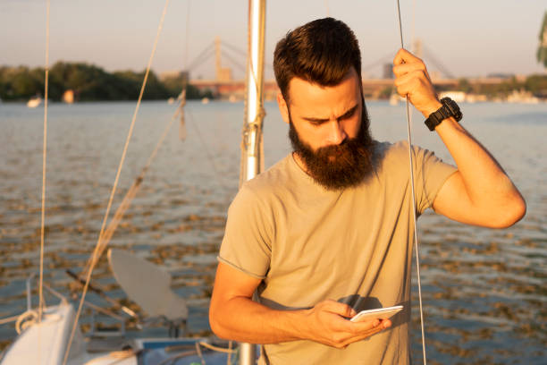 Gut aussehender Mann mit Handy auf Segelboot im Sonnenuntergang – Foto