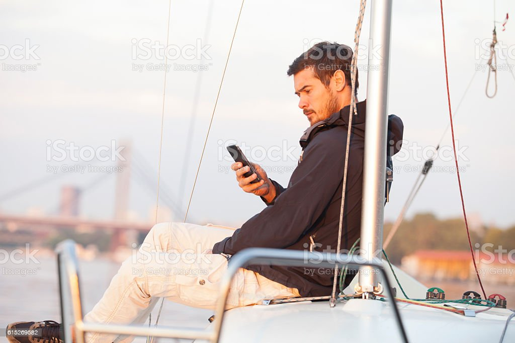 Handsome man using cellphone on sailing boat in sunset – Foto