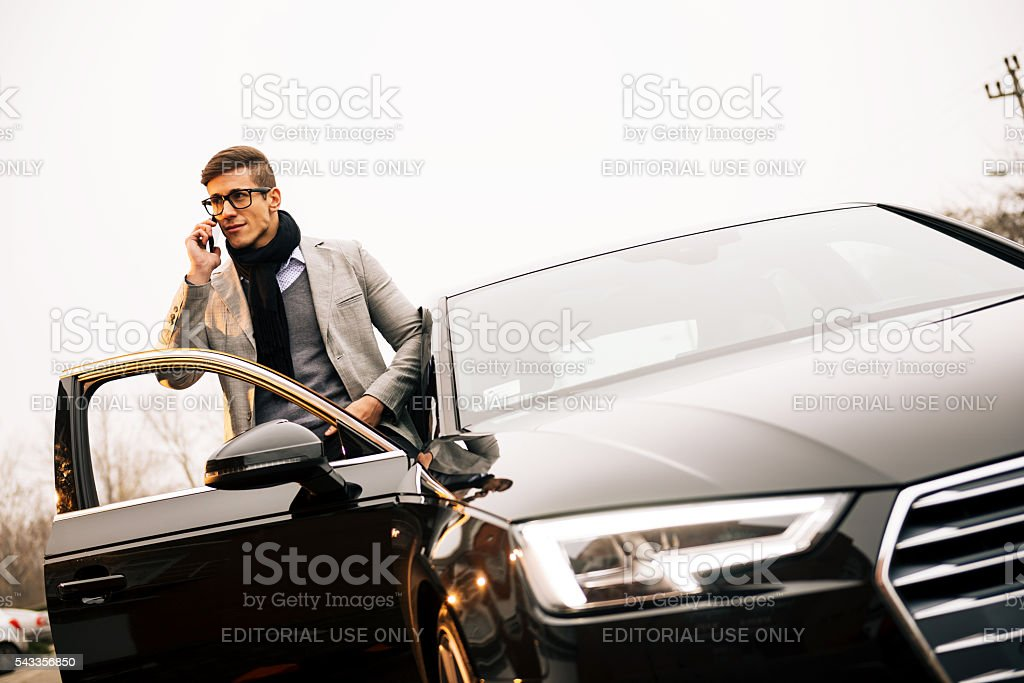 Handsome man using iPhone 6+ and driving new Audi A4 stock photo