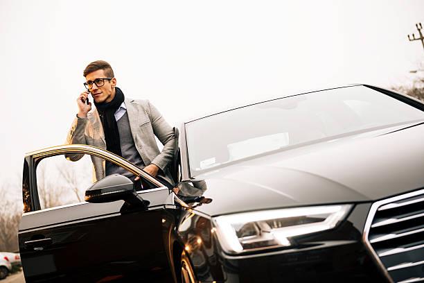 Cтоковое фото Красивый мужчина с помощью iPhone 6 и вождения нового Audi A4