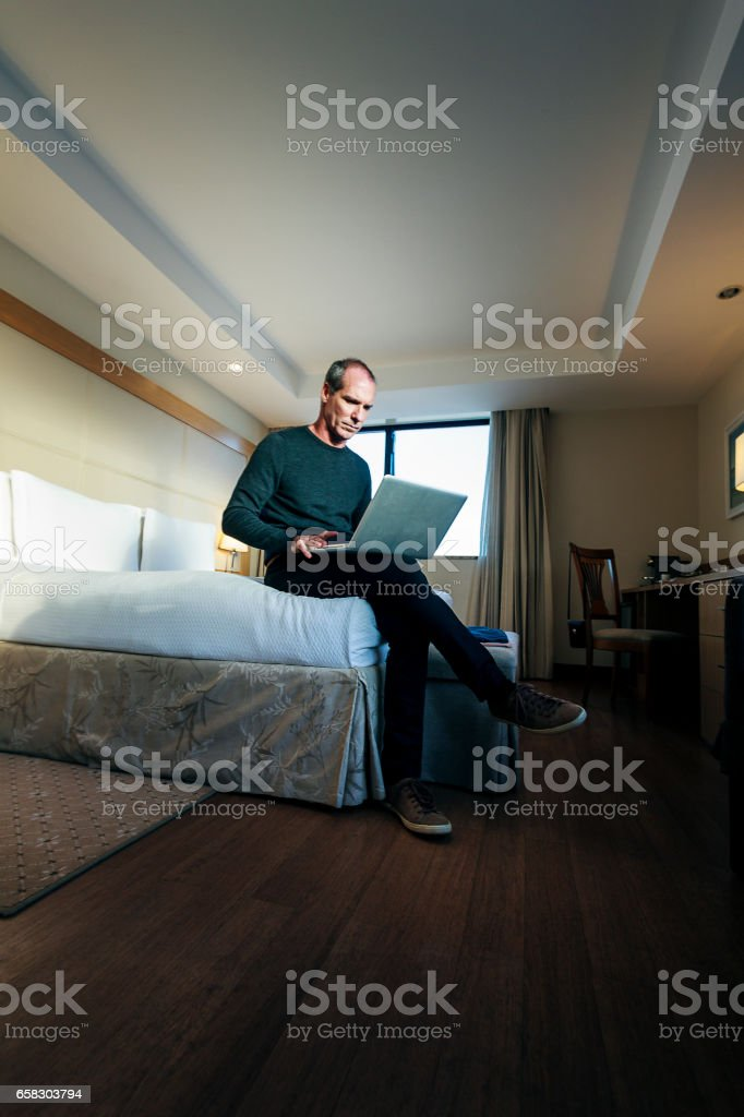 Handsome man using laptop on a hotel room stock photo