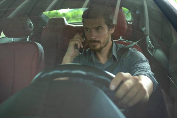 Gut aussehender Mann mit Handy während der Fahrt des Autos – Foto