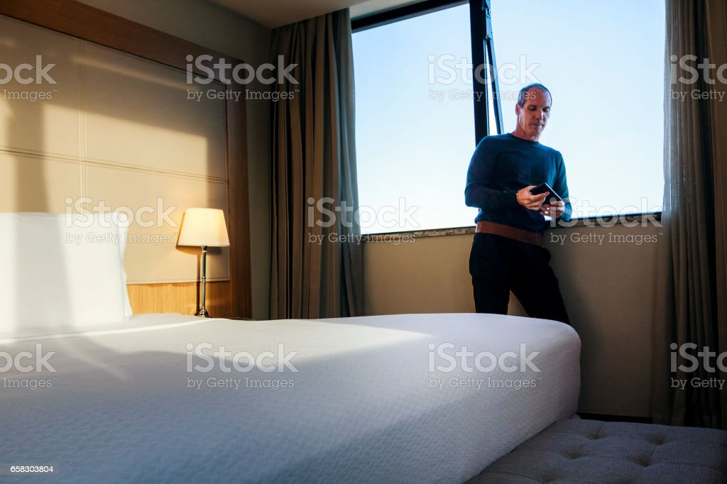 Handsome man using smartphone on a hotel room stock photo