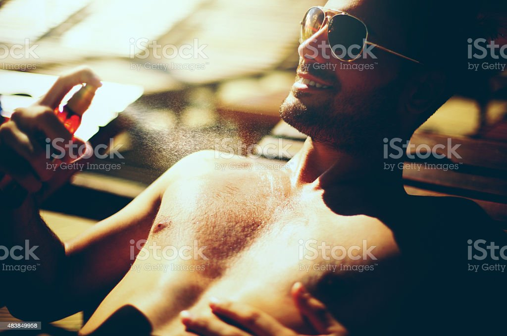 Handsome man using sunscreen. stock photo