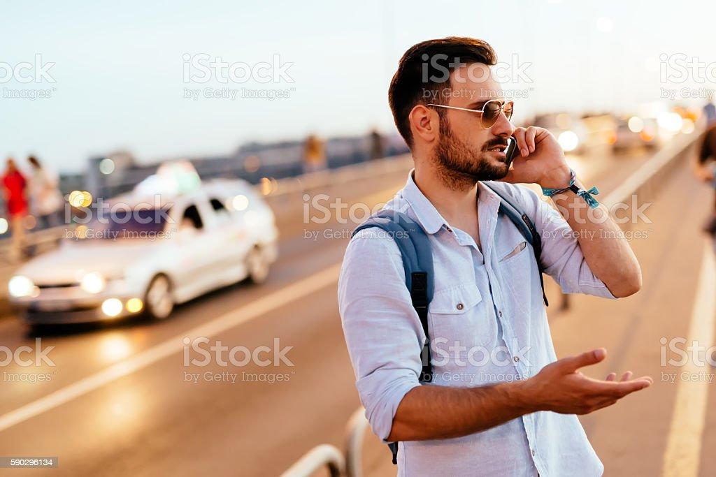 Handsome man waiting for cab royaltyfri bildbanksbilder