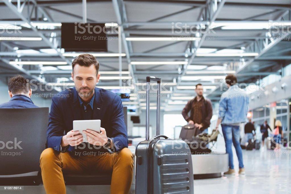 Gut aussehender Mann in Flughafen-Lounge wartet mit einem digitalen tablet Lizenzfreies stock-foto