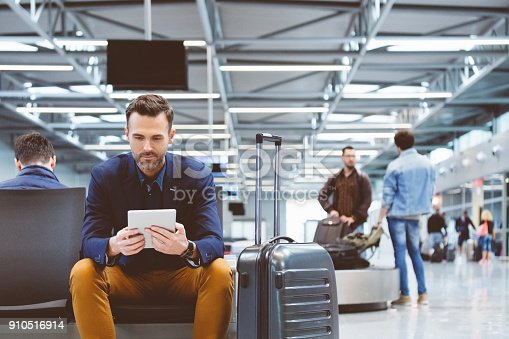 istock Handsome man waiting in airport lounge, using a digital tablet 910516914