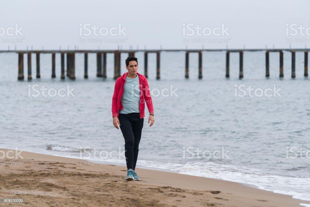 Hombre caminando solo en la playa
