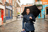 ハンサムな男性のウォーキングを雨から守ります。