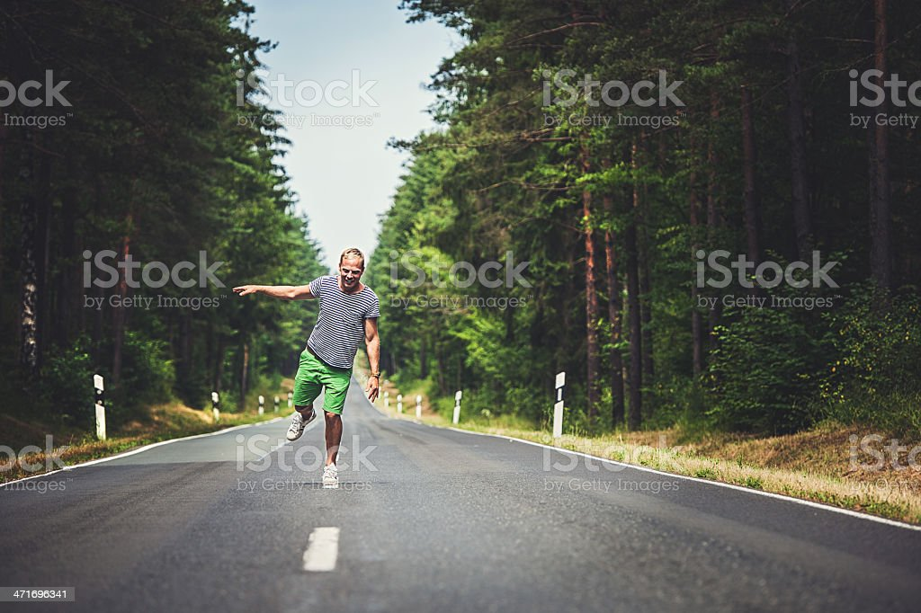 Handsome man walking the line on motorway stock photo