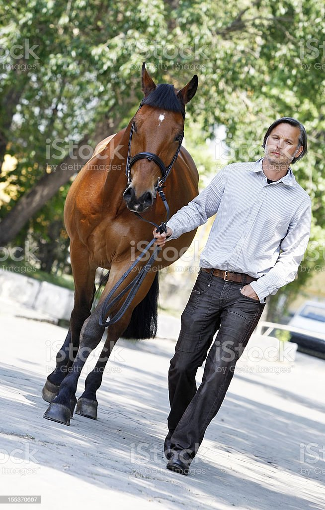 Handsome man walking with his horse royalty-free stock photo