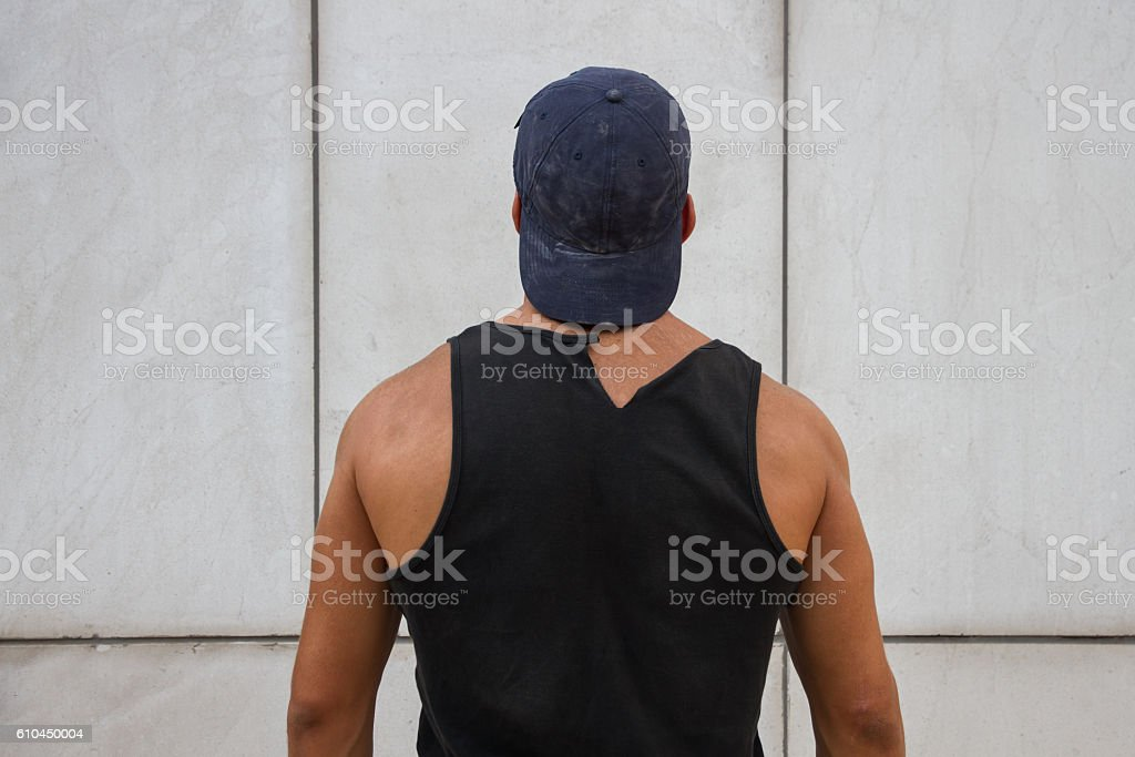 Handsome man wearing a black tank top and a cap. stock photo