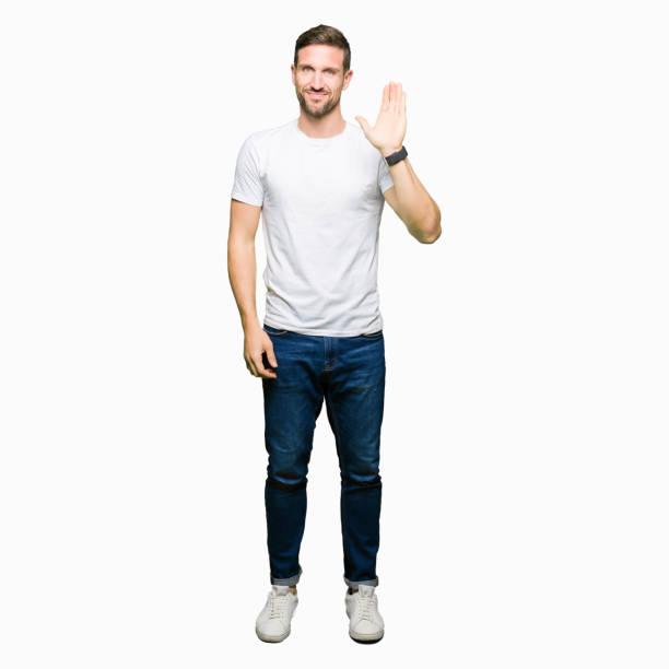 casual beyaz t-shirt waiving mutlu selam ve gülümseyerek, dostça karşılama jest giyen yakışıklı adam - ayakta durmak stok fotoğraflar ve resimler