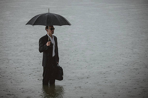 Handsome man wearing suit and holding umbrella during the rain Side view of a handsome man wearing suit and holding umbrella and a briefcase, standing in the water on a rainy day. The man waded knee-deep in water. Selective focus, three quarter length, copy space has been left. wading stock pictures, royalty-free photos & images