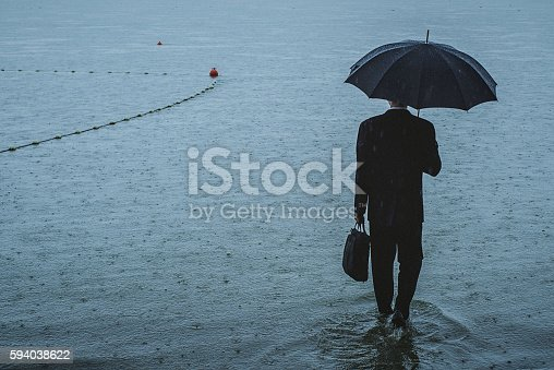 istock Handsome man wearing suit and holding umbrella during the rain 594038622