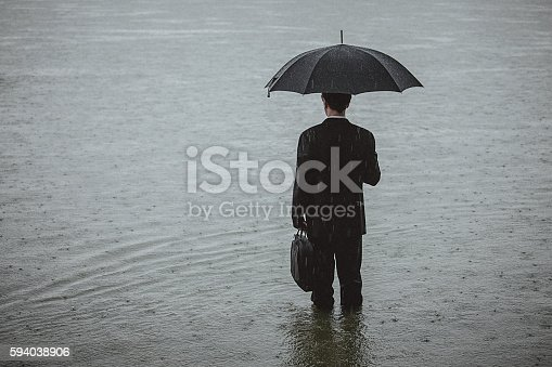 istock Handsome man wearing suit and holding umbrella during the rain 594038906