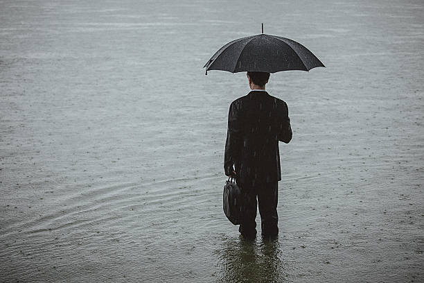 Handsome man wearing suit and holding umbrella during the rain Rear view on a handsome man wearing suit and holding umbrella and a briefcase, standing in the water on a rainy day. The man waded knee-deep in water. Selective focus, three quarter length, copy space has been left. wading stock pictures, royalty-free photos & images