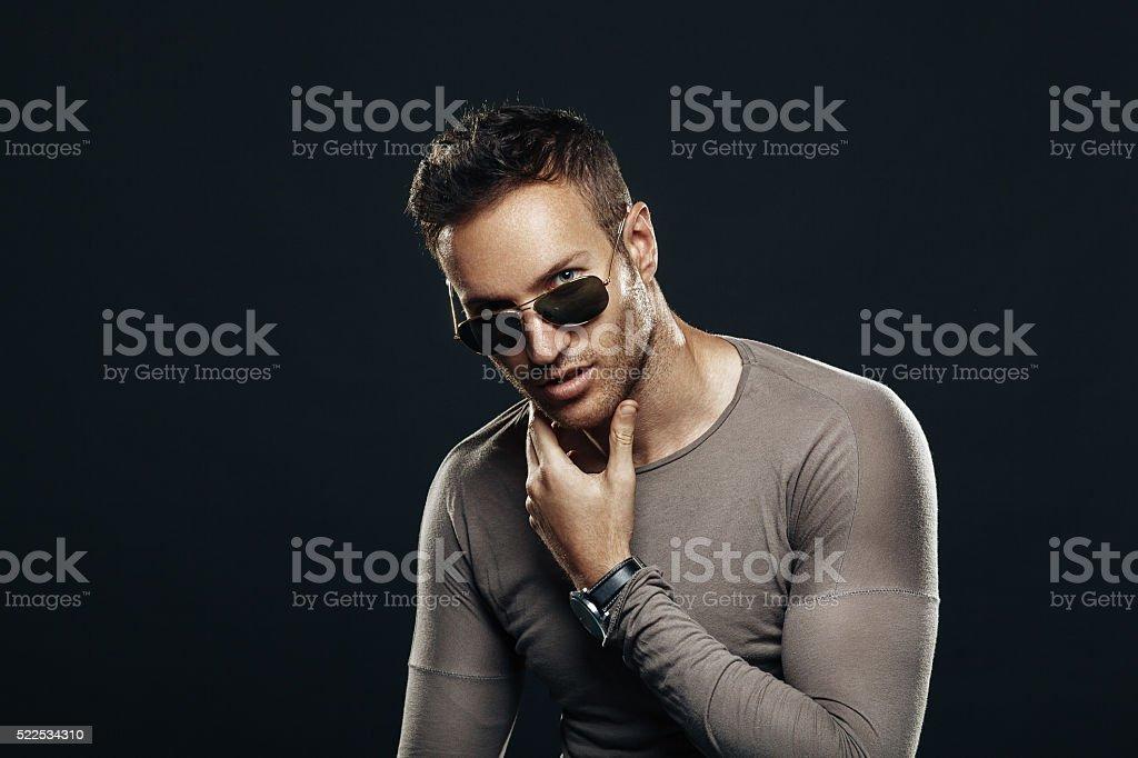 Handsome man wearing sunglasses in the studio stock photo