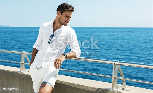 istock Handsome man wearing white clothes posing in sea scenery 537548268