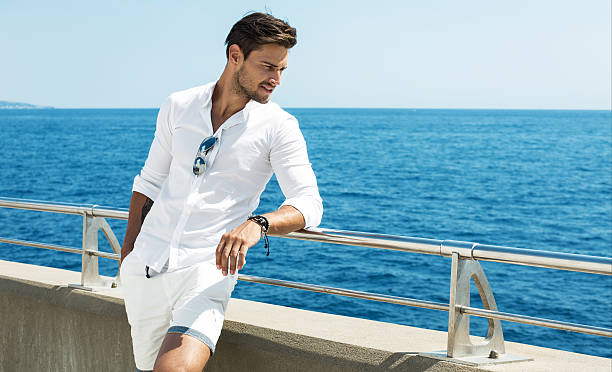 handsome man wearing white clothes posing in sea scenery - handsome people stock photos and pictures