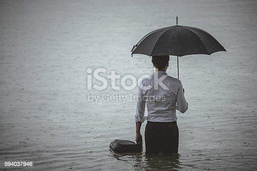 istock Handsome man wearing white shirt and holding umbrella during rain 594037946