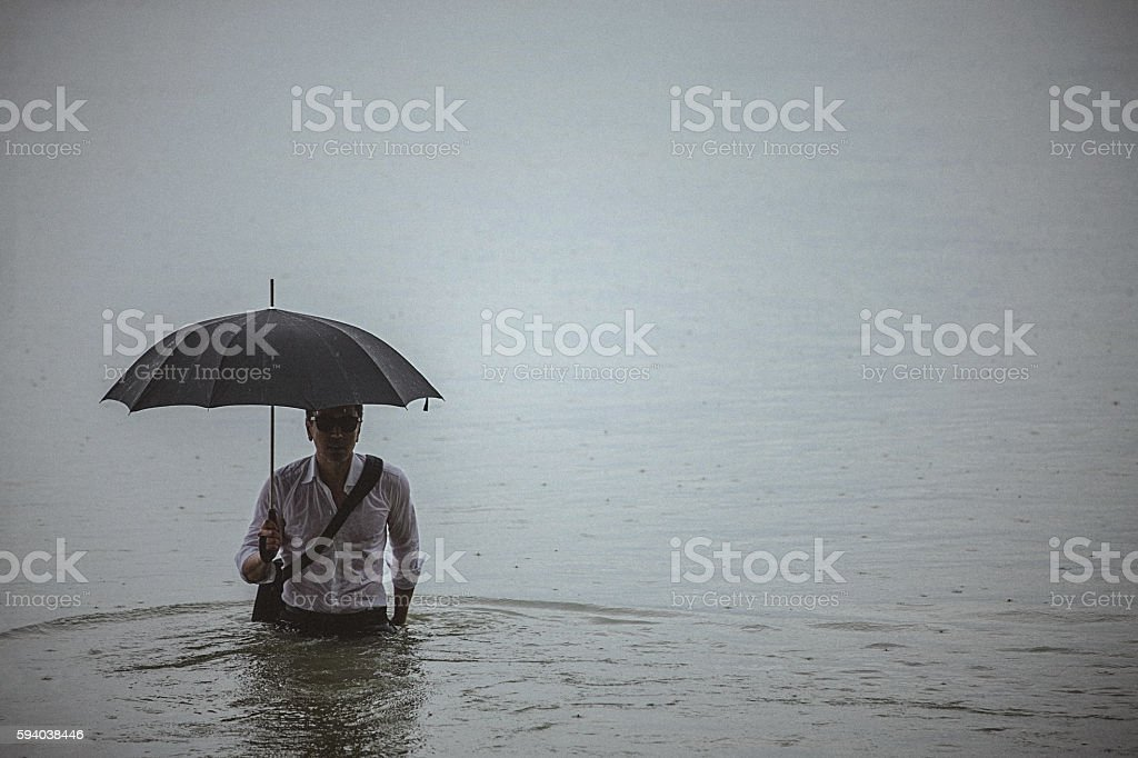 Handsome man wearing white shirt and holding umbrella during rain stock photo