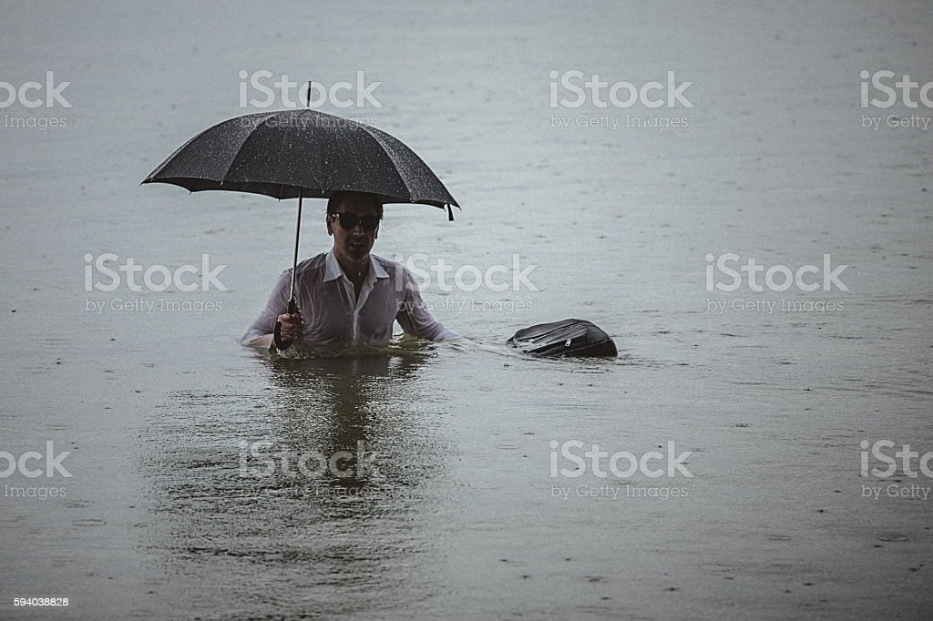 Handsome man wearing white shirt and holding umbrella and a...