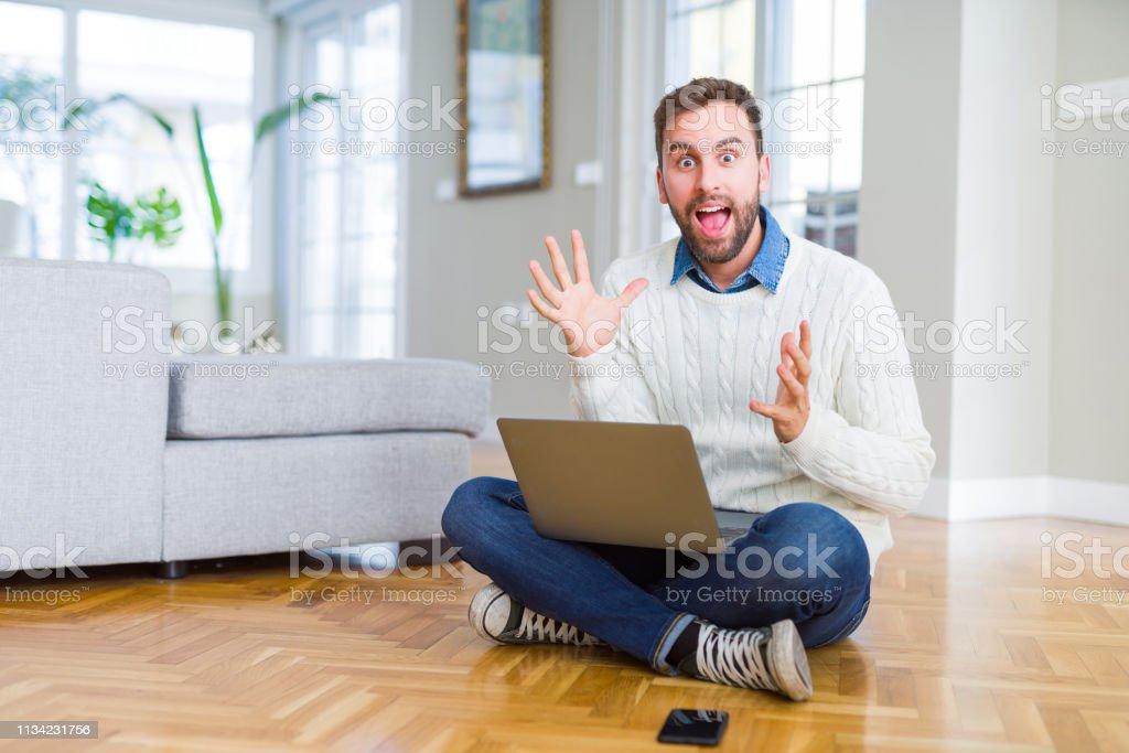 Handsome man wearing working using computer laptop celebrating crazy...