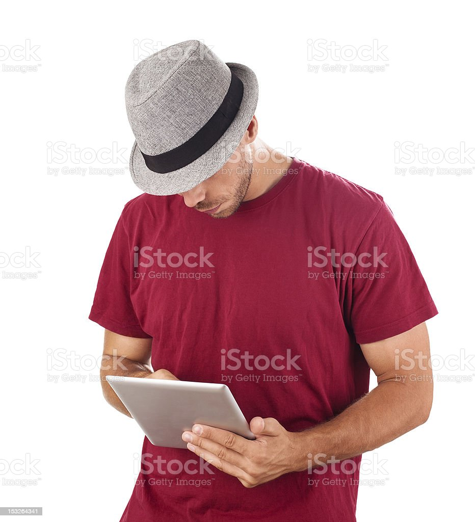 Handsome man with a hat, browsing internet on tablet PC royalty-free stock photo