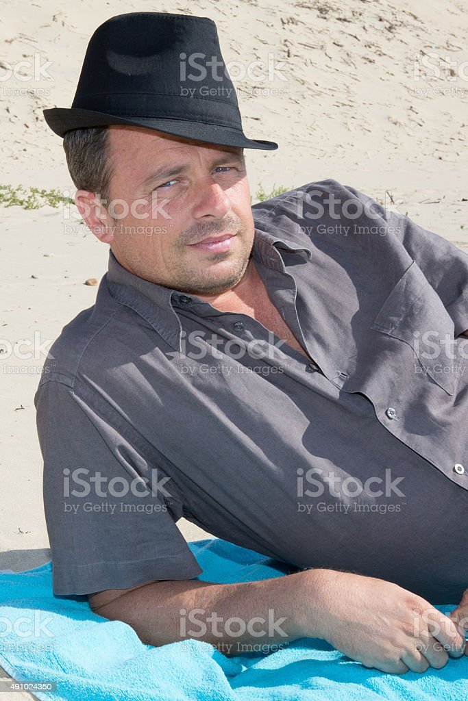 Handsome man with a hat looking at the camera stock photo