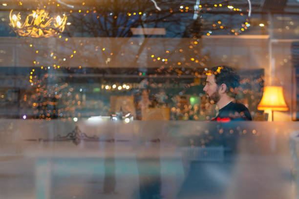 Handsome man with beard in coffee shop with lights reflecting stock photo