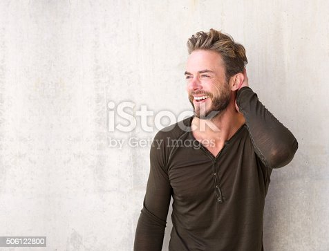 istock Handsome man with beard laughing with hand in hair 506122800