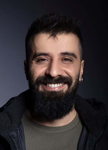 Handsome man with beard looking at camera and laughing.