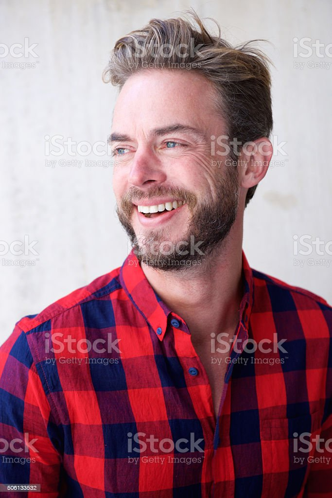 Handsome man with beard smiling and looking away stock photo