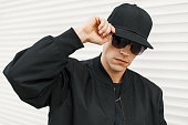 Handsome man with black fashionable glasses and a black baseball cap posing near a white wall
