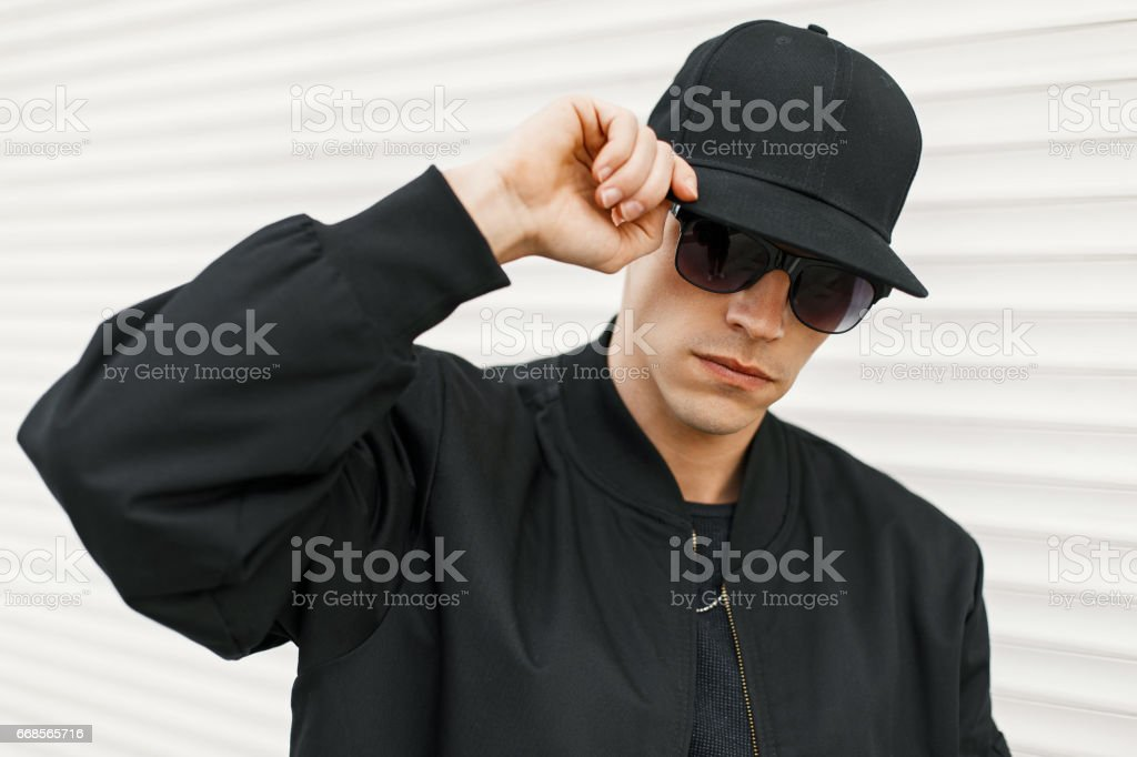 Handsome man with black fashionable glasses and a black baseball cap posing near a white wall stock photo
