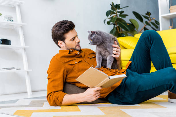 Handsome man with book and lying on floor with cute grey cat picture id1094477076?b=1&k=6&m=1094477076&s=612x612&w=0&h=fat9ol7totv9pfqfno ic vlhey hkjiiijcnjjjuqm=