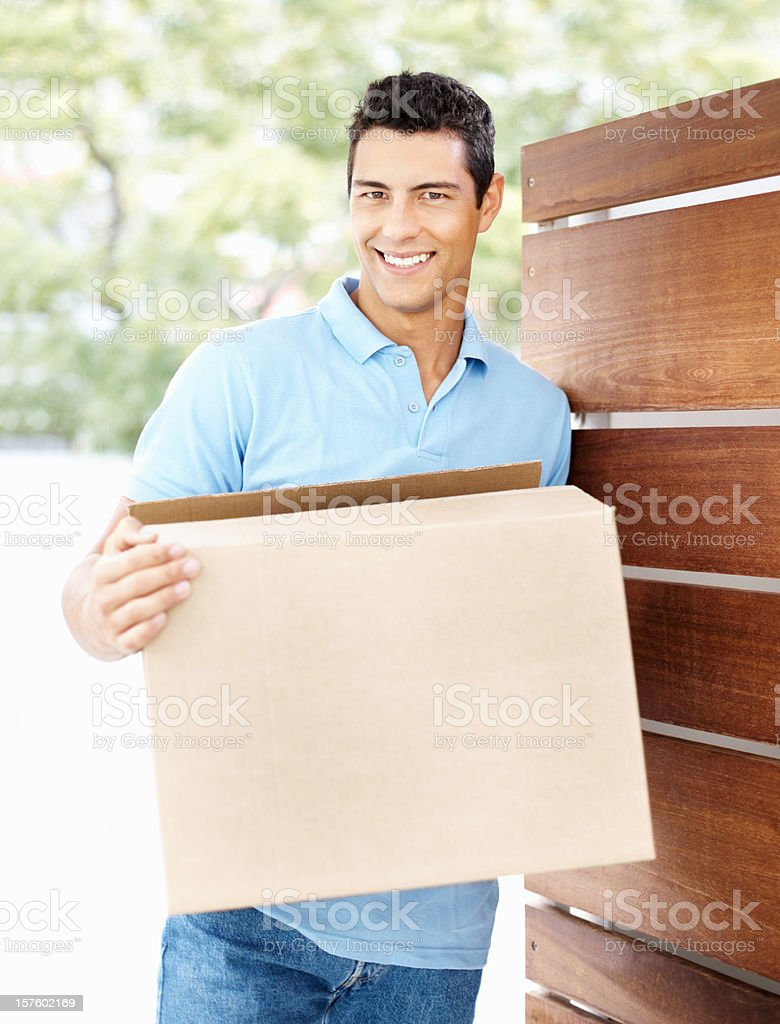 Handsome man with box moving into new apartment royalty-free stock photo