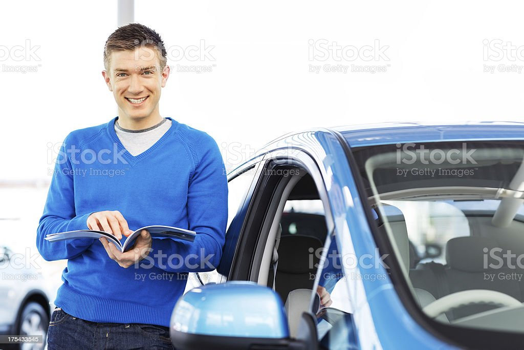 Handsome Man With Brochure Standing By Car royalty-free stock photo