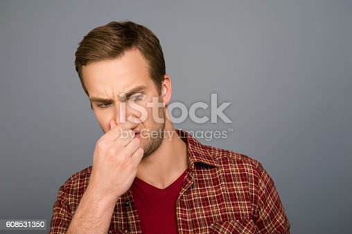 istock handsome man with closed nose because of stink smell 608531350