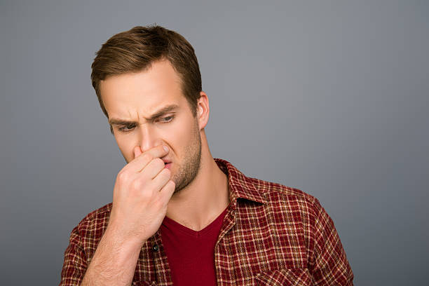 handsome man with closed nose because of stink smell stock photo