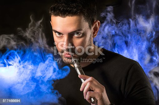 689660424 istock photo Handsome man with e-cirarette in a vapor 517466694