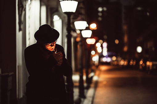 Portrait of a handsome young male model wearing black hat and long black coat, he is standing on city street at night and lighting cigarette.