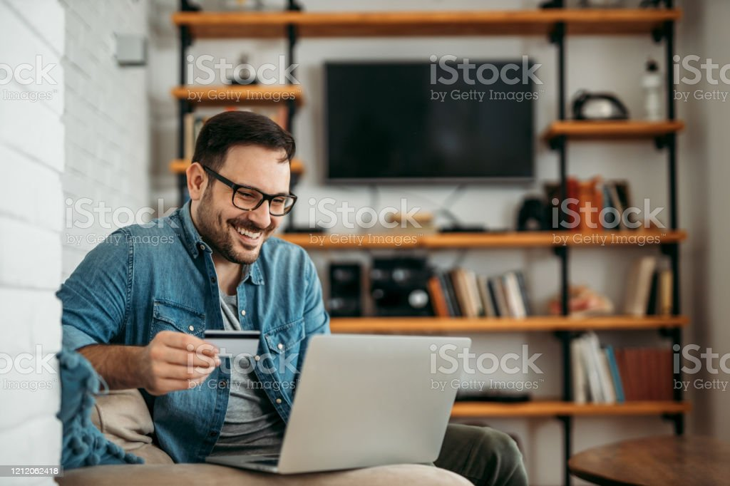 Handsome man with laptop and credit card at home, portrait. Handsome man with laptop and credit card at home, portrait. Adult Stock Photo
