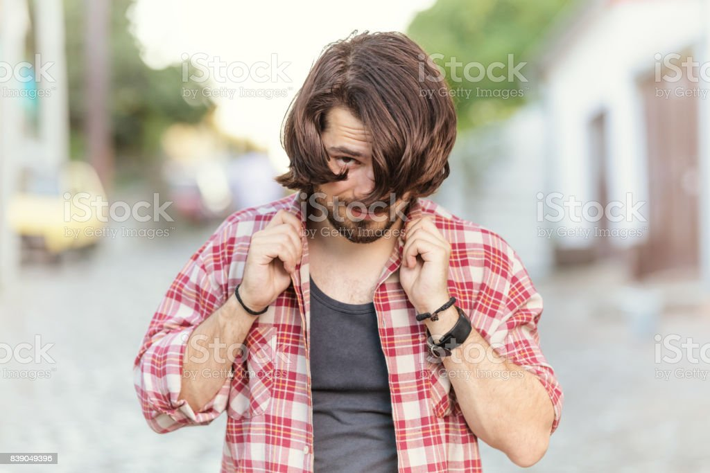 Handsome man with long hair posing on the street. stock photo