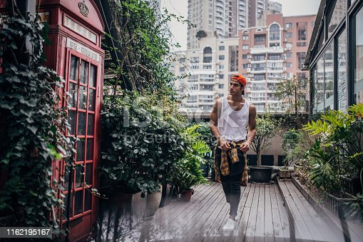 Handsome man with white tank top and orange cap standing outdoors portrait. .