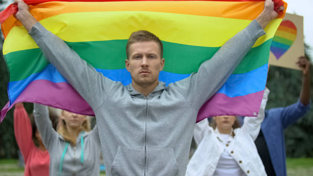 Handsome man with rainbow flag amid protesters for gay rights, LGBT pride event Handsome man with rainbow flag amid protesters for gay rights, LGBT pride event amid stock pictures, royalty-free photos & images