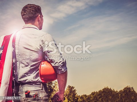 Handsome man with tools, holding an American Flag, standing against a background of green trees and the rays of the setting sun. View from the back, close-up. Concept of work and employment